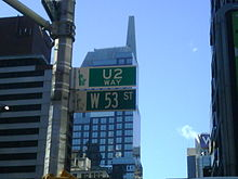"A green street sign with 53rd Street written on it. Just above the sign is another, identical in colour, which says ""U2 Way"". A skyscraper with reflective windows is immediately behind the signs."