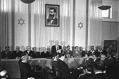 A single man, adorned on both sides by a dozen sitting men, reads a document to a small audience assembled before him. Behind him are two elongated flags bearing the Star of David and portrait of a bearded man in his forties.