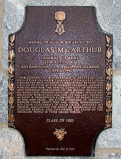 A bronze plaque with an image of the Medal of Honor, inscribed with MacArthur's Medal of Honor citation.