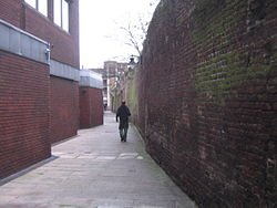 A view down an alleyway, bounded by a red brick wall on the right, and red brick buildings on the left.