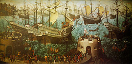 A small fleet of large, highly decorated carracks are riding on a wavy sea. In the foreground are two low, fortified towers bristling with cannons and armed soldiers and retinue walking between them.