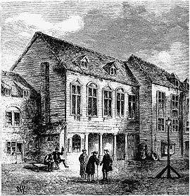 Three two-storey buildings in a staggered row, each with mullioned windows and the central one with a four-columned entrace. Three standing men converse in the courtyard in front, and two men sit at a bench, one drinking and gesturing.