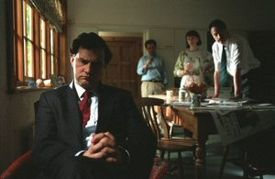 A man wearing a suit sits on a chair. Two men and a woman stand behind him.