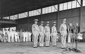 MacArthur stands in uniform at four microphones on stands. Behind him four men in army uniforms stand at attention. There are viewed by a large crowd of well-dressed men, women and children in skirts, suits and uniforms.