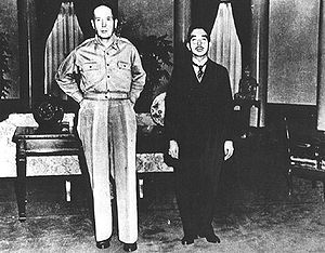 MacArthur, without hat and wearing open necked shirt and trousers, towers over an oriental man in a dark suit.