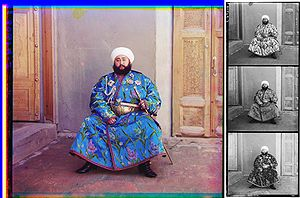 A large color photograph abutting (to its right) a column of three stacked black-and-white versions of the same picture.  Each of the three smaller black-and-white photos are slightly different, due to the effect of the color filter used.  Each of the four photographs differ only in color and depict a turbaned and bearded man, sitting in the corner an empty room, with an open door to his right and a closed door to his left.  The man is wearing an ornate full-length blue robe trimmed with a checkered red-and-black ribbon.  The blue fabric is festooned with depictions of stems of white, purple, and blue flowers.  He wears an ornate gold belt, and in his left hand he holds a gold sword and scabbard. Under his right shoulder strap is a white aiguillette; attached to his robe across his upper chest are four multi-pointed badges of various shapes, perhaps military or royal decorations.