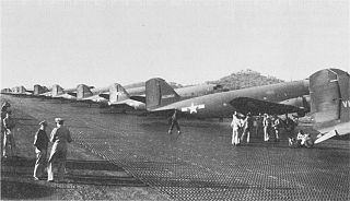A steel plank runway with identical aircraft lined up along its length at right. Two small figures stand off to the left of the runway.